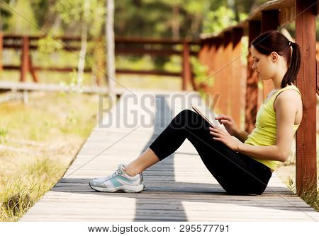 Young woman sitting outdoor with tablet. Outdoor internet concept.
