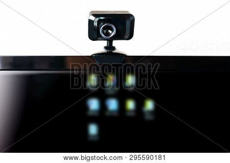 USB Webcam, Web Camera, Mounted on Computer Monitor with Blurred Icons on Black Screen. Data Protection, Cyber Security, Online Privacy. Social Media Disinformation Concept. poster