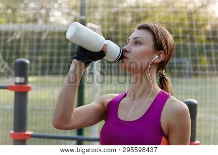 Attractive Young Swart Woman In Bright Sportswear Drinks Water During Fitness On Outdoors Sportsgrou