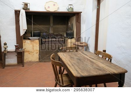 Basic Old Vintage Kitchen With Rustic Wood Table Wood-burner And White Walls : Rudimentary Comfort C
