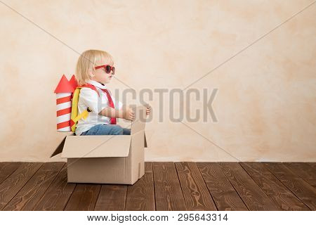 Happy Child Playing With Toy Rocket At Home. Funny Kid Driving Cardboard Box Indoor. Success And Win