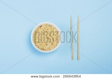Asian Instant Noodles On A White Plate And Chinese Sticks On A Blue Background. The Concept Of Conve