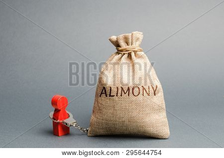 The Man Is Handcuffed To A Money Bag With The Word Alimony. The Concept Of Child Support. Payments A