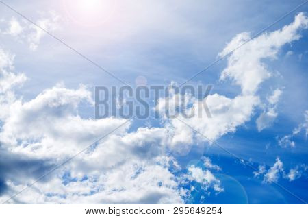 Blue sky background with white dramatic colorful clouds and sunlight. Sky landscape scene, blue sky background with white clouds in the sky lit by sunlight. Natural sky background, sky sunny landscape