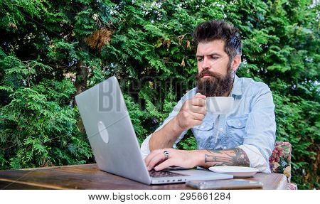 Work And Play Give Him Rest And Energy. Bearded Man Doing His Work Online. Hipster Drinking Tea And