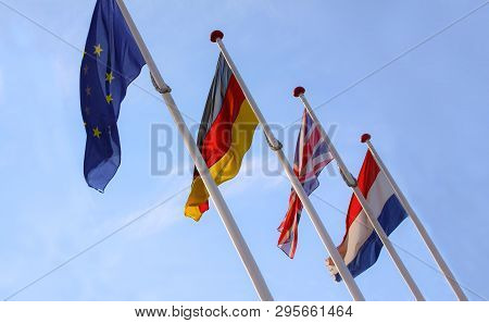 Flags from England, United Kingdom, Germany and Nederlands waving from flagpoles together with the EU, European Union, flag against a blue sky.