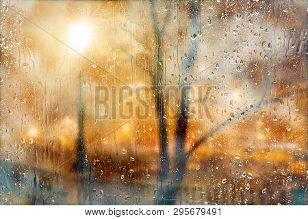 Abstract Background Of Night City Street Raining Through The Window.rainy Night And Town Lights