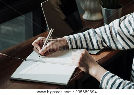 Close Up Of Woman's Hands Writing In Spiral Notepad Placed And Laptop Computer On Wooden Table