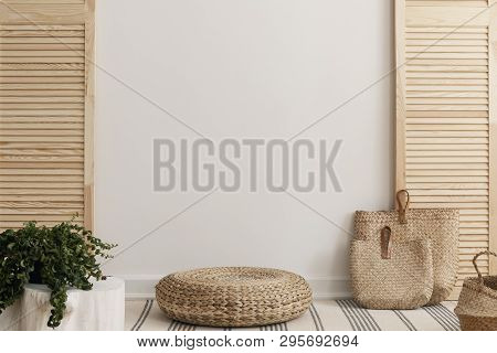Empty White Wall Between Wooden Screen In Bright Interior With Wicker Pouf And Straw Bags