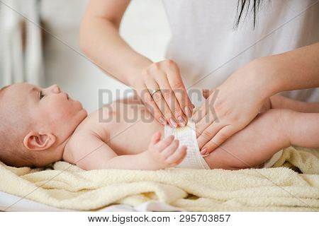 Close Up Of Hands Fix Diaper On Baby Waist