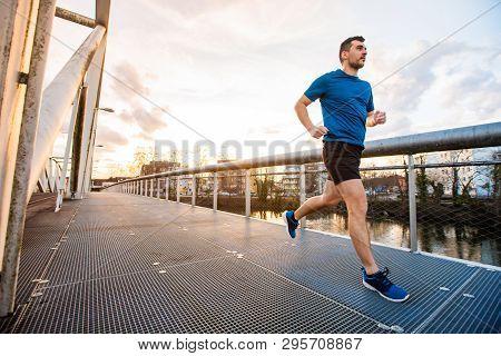 Running Man Runner Training Doing Outdoor City Run Sprinting Over A Bridge. Urban Healthy Active Lif