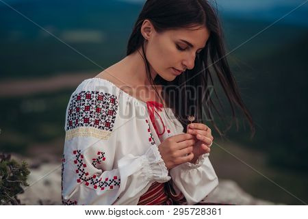 Atractive Woman In Traditional Romanian Costume On Mountain Green Blurred Background. Outdoor Photo.
