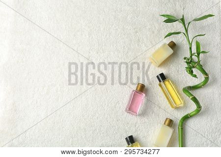 Mini Bottles With Cosmetic Products On Towel, Top View And Space For Text. Hotel Amenities