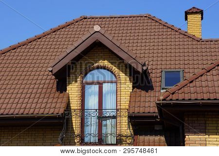 Open Balcony On The Brick Wall Of The House Under The Brown Tiled Roof Against The Sky