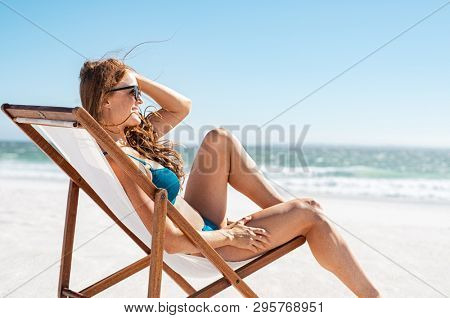 Smiling woman sunbathing on deck chair at beach. Attractive mature woman relaxing at seaside and looking the ocean. Young happy girl in bikini lying on a sun chair while wearing sunglasses.