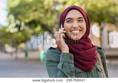 Beautiful and happy woman in hijab talking over mobile phone. Portrait of arabic woman in religious headscarf talking on cellphone. Smiling islamic girl with hijab looking away while talking on phone.