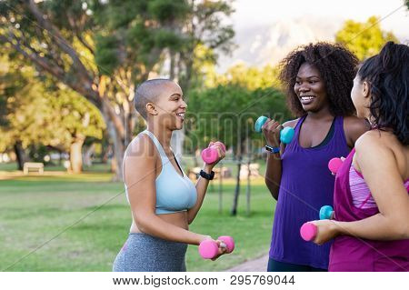 Fitness curvy group lifting hand weights at park. Team of three curvy women using weights outdoor for fitness exercise. Smiling oversize muliethnic girls using dumbbells for workout in park.