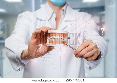 A Closeup Of A Doctor Holding A Denture Model Surrounded With Wireless Connections And Question Mark