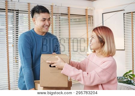 Happy Asian Couple Carry Cardboard Boxes While Moving To New House In Living Room.unpacking For New