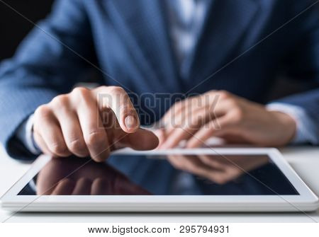 Close-up Of Male Hand Touching Screen Of Digital Tablet. Man In Business Suit Sitting At Desk And Wo