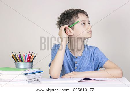 Kid Doing Homework At The Table. Boy With Pencil Behind His Ear Thinking Or Dreaming And Looking Awa