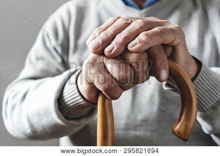 Close Up Details Of The Folded Hands Of An Elderly Man Resting On A Walking Cane In A Mobility And H