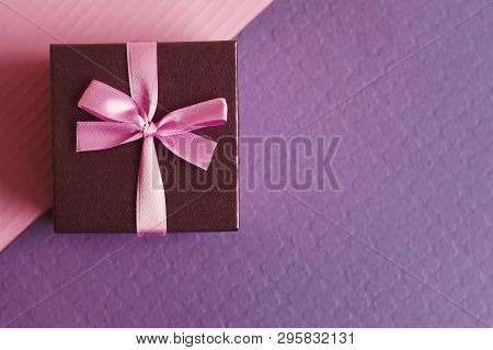 Small Decorative Gift Box With Pink Ribbon On Purple (violet) And Pink Background, Top View. Present