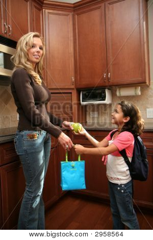 Woman Giving Lunch To Child