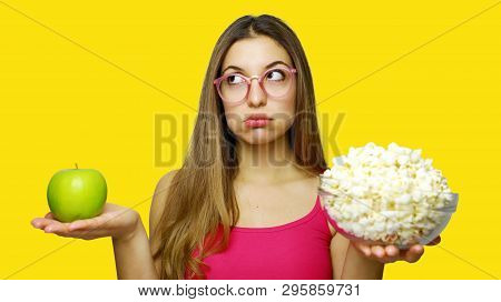 Woman Choosing Between Unhealthy Bowl Of Pop Corn And An Healthy Green Apple Looking To The Side. Gi