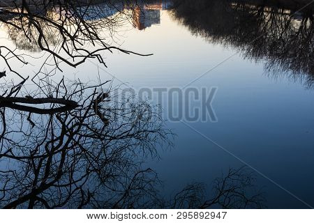 Beautiful Reflection Of Trees And High-rise Building In The Mirror Smooth Surface Of The River.