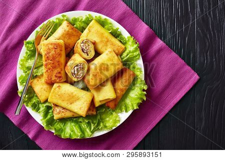 Overhead View Of Savory Crepe Rolls With Ground Chicken Meat And Champignon Filling Served On A Bad