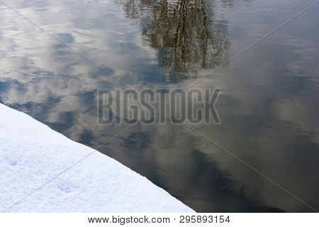 Abstract Reflection Of Clouds And Trees In The Water And The Edge Of The Snow.