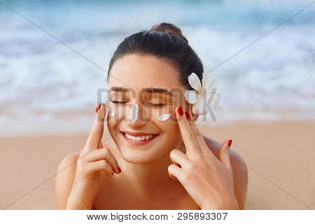 Beautiful Woman Applying Cream Sunscreen On A Tanned Face. Sunscreen. Skin And Body Care. The Girl U