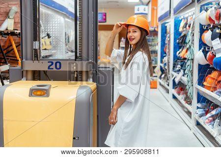Woman In Orange Construction Helmet At Supermarket Blur Background