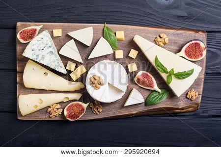 Cheeseboard With Cheese Brie , Parmesan , Camembert And Dorblu . Food On Wooden Board