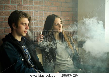 Vape Teenagers. Young Cute Girl In Sunglasses And Young Handsome Guy Smoke An Electronic Cigarettes