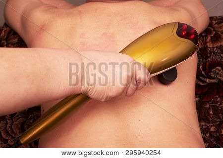 Senior male patient receive electrostatic therapy procedure on his back. Electrostimulation massage close-up. woman doing massage with electric massager for male poster