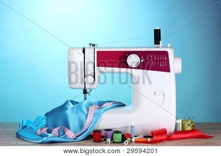 máquina de coser y la tela en fondo azul