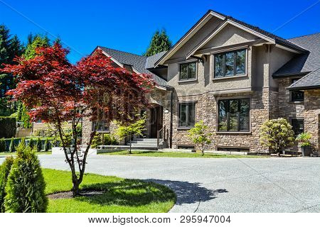 Front Yard Of Luxury Family House With Green Lawn And Concrete Driveway In Front On Blue Sky Backgro
