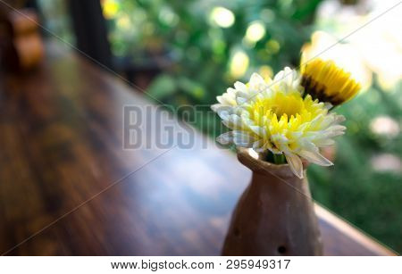 Yellow Flowers In A Ceramic Vase On The Wooden Table With Garden Background Out Of Focus
