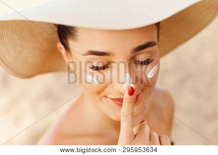 Beautiful Young Woman With Sun Cream On Face. Girl Holding Sunscreen Bottle On The Beach. Female In