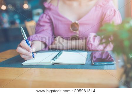 The Woman's Hand Is Writing On A Notebook With A Pen.