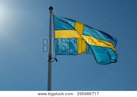 The Flag Of Sweden Close Up Waving In The Wind With A Clear Blue Sky.