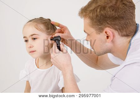 The Young Sympathetic Otolaryngologist Examines The Ears Of A Girl - A Girl Of School Age. People Is