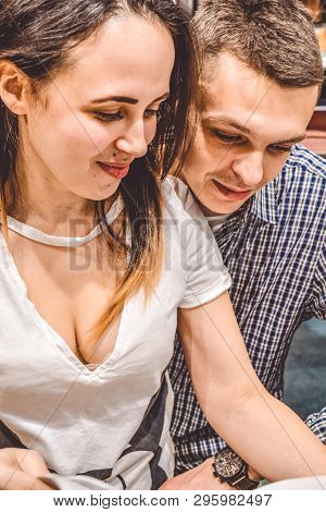 Young Married Loving Couple Sit And Read The Magazine. Thumb Through The Brochure And Choose Goods F