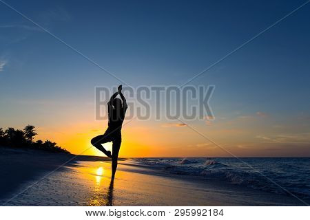 Yoga Vrikshasana Tree Pose By Woman In Silhouette On The Beach With Sunset Sky Background. Free Spac