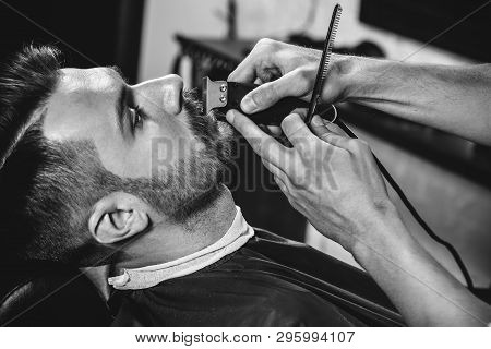 Client During Beard Shaving In Barbershop. Young Handsome Barber And Attractive Bearded Man. Black A
