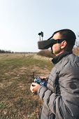 FPV drone pilot in a virtual reality helmet with a remote control from a copter flies in aircraft outdoor poster