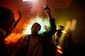Crowd of cheerful hilarious young multiethnic people drinking alcohol and dancing in smoke at noisy party poster