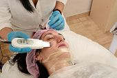 Young woman in beauty salon doing ultrasound peeling and facial cleansing procedure. poster